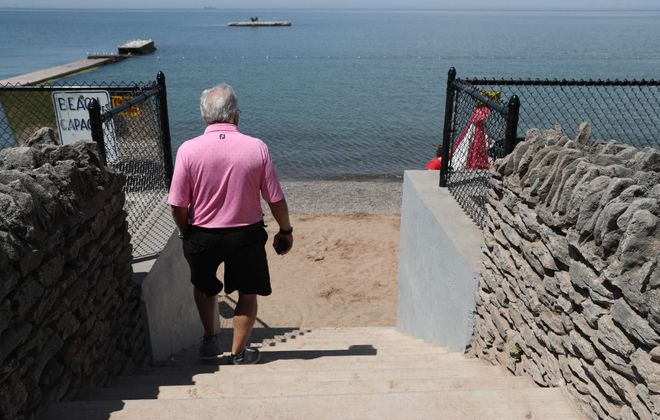 A man walks down the stairs to Olcott Beach on June 12, 2018. The water levels in Lake Ontario are 22 inches lower this year. (Sharon Cantillon/Buffalo News)