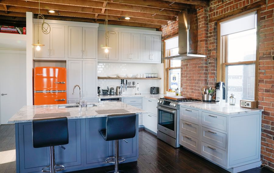 High, exposed-beam ceilings and soaring windows lend light and spaciousness to the kitchen, while a new dark-stained hardwood floor connects all the rooms. Custom-built cabinets by Wrafterbuilt. (Dave Jarosz)