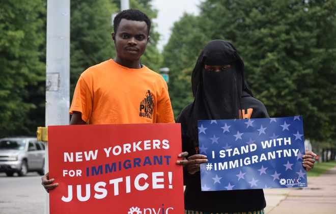Isaac Asumani, left, a refugee of the Democratic Republic of the Congo, and Kawiye Jumale, right, a refugee of Somalia, hold pro-immigration signs at the Delaware Avenue and Summer Street intersection. (Sam Ogozalek/Buffalo News)