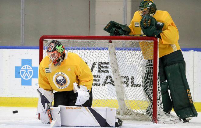 Ukka-Pekka Luukkonen, left works with camp invitee Jake Rielly prior to practice Friday in HarborCenter. (James P. McCoy/Buffalo News)