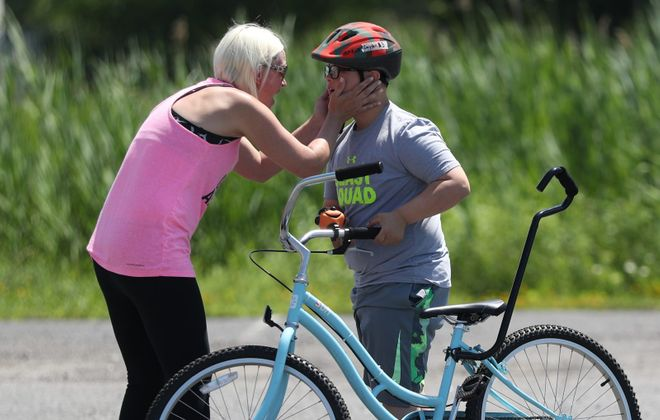 Katie Luciano congratulates her 11-year-old son Cayden after he makes a solo ride at the Western New York iCan Bike Camp in West Seneca. (Sharon Cantillon/Buffalo News)