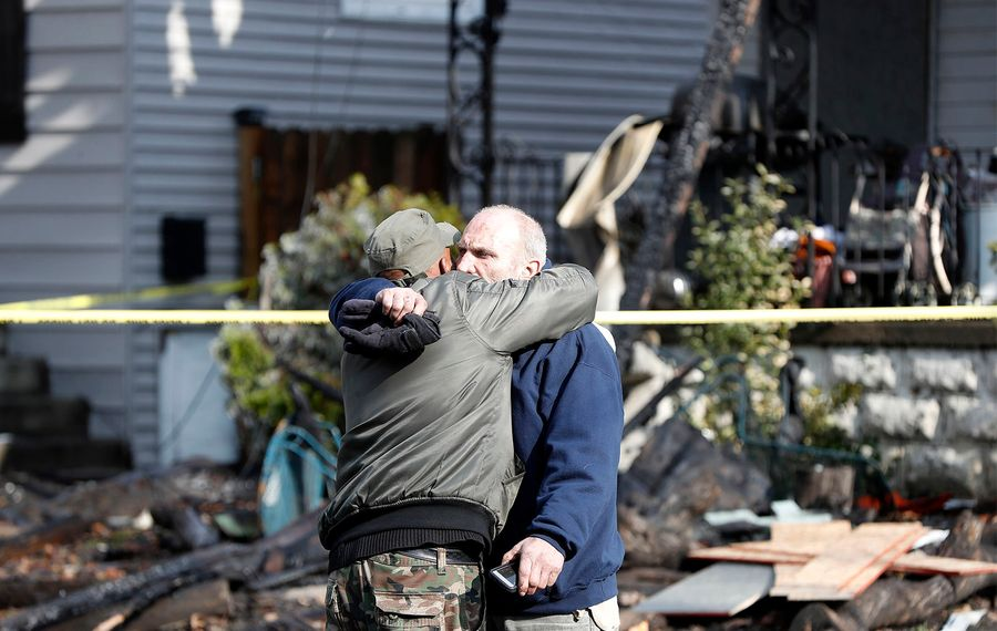Joseph Conti hugs his neighbor in front of his home on Benzinger Street in Buffalo on Monday, Jan. 29, 2018. The early morning fire took the life of Conti's 7-year-old son. (Mark Mulville/News file photo)