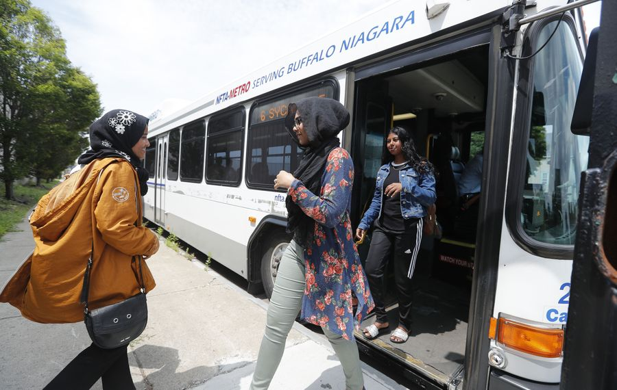 Buffalo Public Schools students Tahmina Aktar, left, Maimuna Manna, center, and Morzina Sarker get off a packed NFTA bus. The School District and NFTA need to negotiate a less expensive, more flexible agreement for student transportation. (Mark Mulville/Buffalo News)