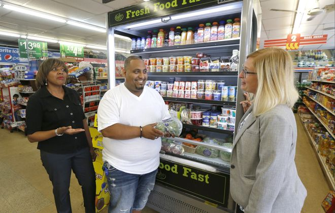 "Trade Fair Food Market owner Adel Munassar, center, discusses healthy food options in front of one of his ""Fresh Fast Food"" refrigerated cases with Sheila Bass and Annie Todd at his store on East Delavan Avenue in Buffalo.  (Robert Kirkham/Buffalo News)"