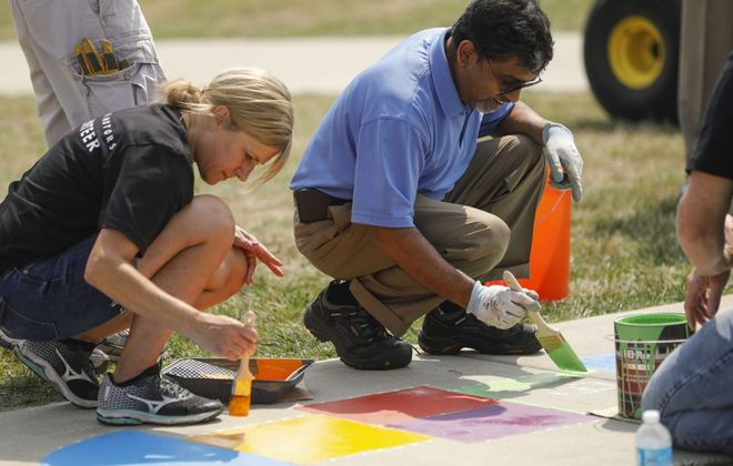 """Gina Moell of the GM Tonawanda Engine Plant, left, and Plant Director Ram Ramanujam, paint a hopscotch grid on the sidewalk while helping to create a new """"Born Learning Trail,"""" a series of 10 signs and corresponding activities for children on the sidewalk around the playground at Buffalo Outer Harbor State Park as part of the United Way Day of Caring. (Derek Gee/Buffalo News)"""