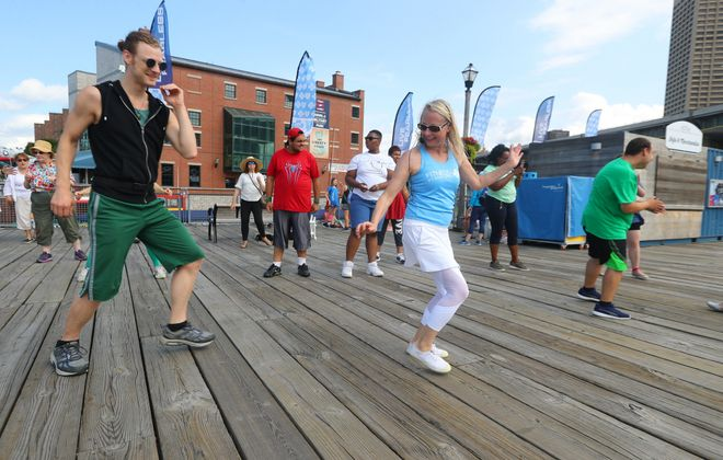 Cynthia Cadwell Pegado, right, pictured with Phil Wackerfuss, left, has drawn a healthy number of people to her Friday morning dance classes at Canalside. After a break in the classes this week, they will take place Aug. 10, 24 and 31.   (John Hickey/Buffalo News)