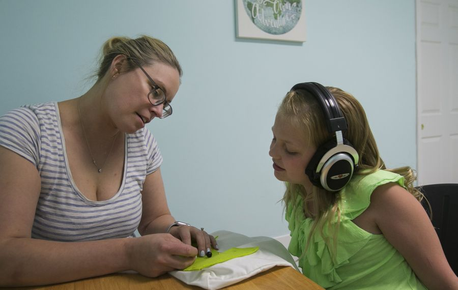 """""""""""Your brain can grow and change – and you've got to challenge it,"""" says Sarah Smith, owner of Kinesthetic Listening Center of Western New York in East Aurora. She is pictured helping Olivia Greiner during a recent craft session. (Shuran Huang/Buffalo News)"""