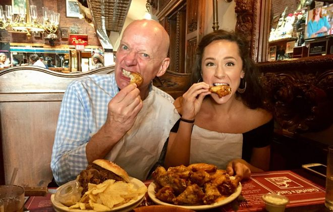 "Jonathan Weir and Lissa deGuzman, Jafar and Jasmine in ""Aladdin,"" dive into a plate of chicken wings at Gabriel's Gate. (Francesca Bond/The Buffalo News)"