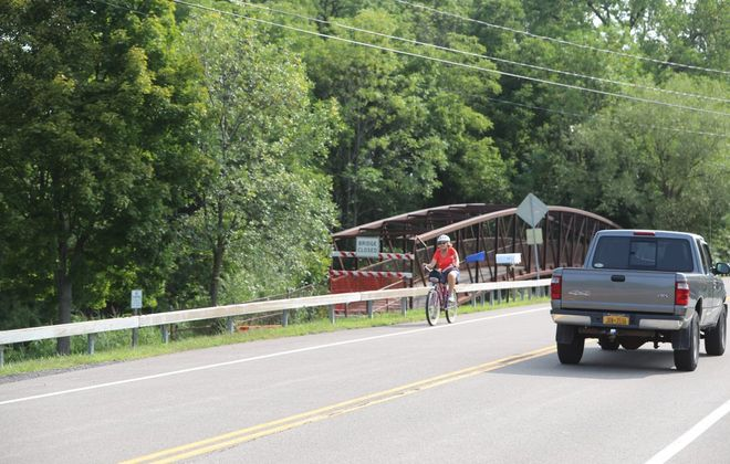 The Town of Amherst in August 2018 shut down the pedestrian bridge on the Erie Canal Trailway over Ransom Creek due to safety concerns. This bicyclist is riding on the shoulder of the adjacent Tonawanda Creek Road bridge. Crews will replace the pedestrian bridge this weekend. (John Hickey/News file photo)