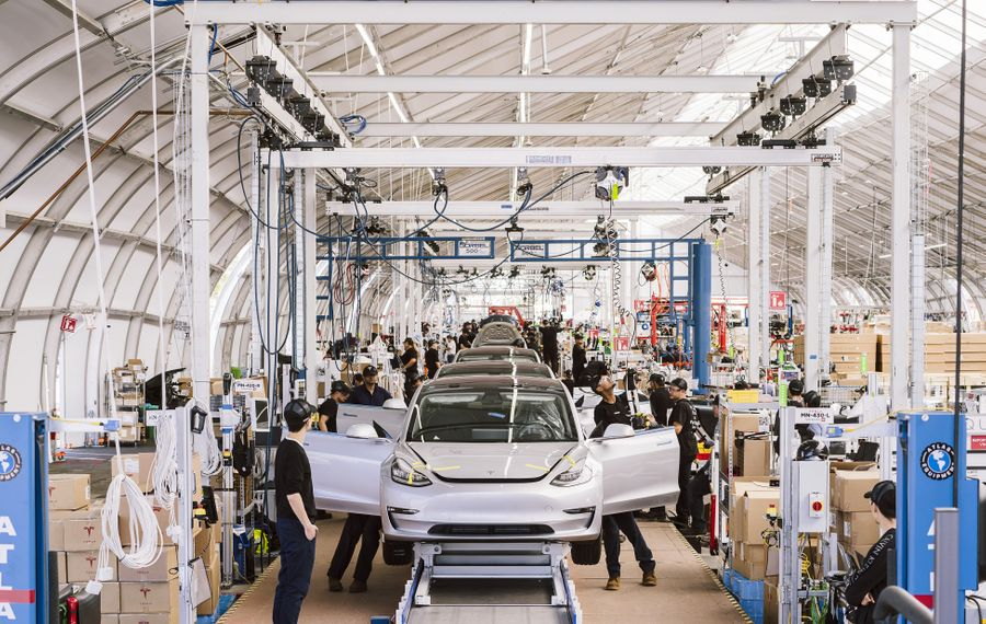 Workers on the Tesla Model 3 assembly line at Tesla's factory, in Fremont, Calif. Ramping up production of the Model 3, its first mass-market offering, has forced the company to consume hundreds of millions of dollars in cash. (Justin Kaneps/The New York Times)