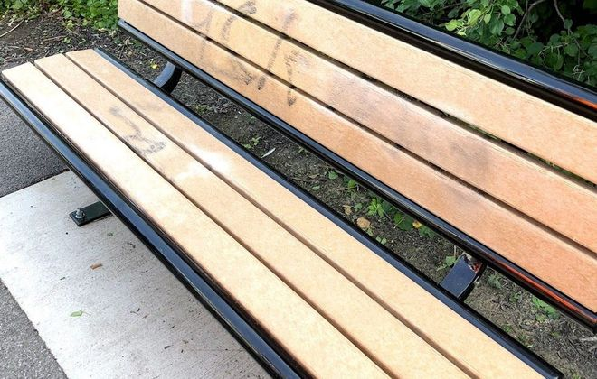This shows the graffiti that marred the Rails to Trails path in the City of Tonawanda after a city worker had cleaned some of it from this bench as of Tuesday morning. (Stephen T. Watson/Buffalo News)
