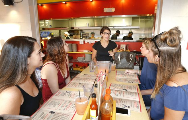 Server Lindsey Abbott, center, explains Taco Tuesday to Deep South Taco customers. (Robert Kirkham/News file photo)