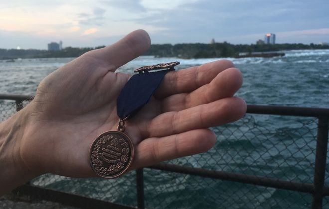 Dan Hill holds a medal for bravery awarded to his grandfather, Red Hill Sr., by the Royal Canadian Humane Association. In the background is a scow stranded near Niagara Falls for a century. Red Sr. played a key role in saving two men stranded on the vessel in 1918. (Sean Kirst/Buffalo News)