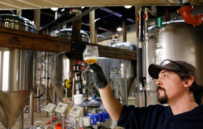 Matt Redpath, head brewer at Woodcock Brothers Brewery in Wilson, examines the first glass of new tank of XPA. (Derek Gee/Buffalo News)