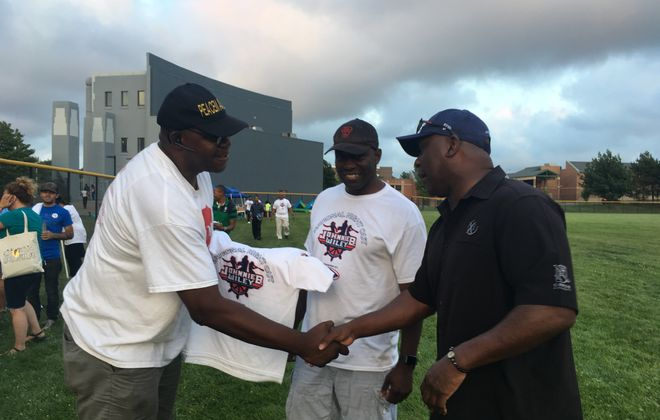 Longtime anti-violence activist Murray Holman reaches out to shake the hand of Thurman Thomas, Buffalo businessman and football Hall of Famer, as Buffalo police detective Cedric Holloway looks on during a gathering at national Night Out in Buffalo. (Sean Kirst/The Buffalo News)