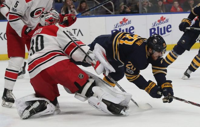 Buffalo Sabres center Scott Wilson (20) gets tripped by Carolina Hurricanes goalie Cam Ward. (James P. McCoy/News file photo)