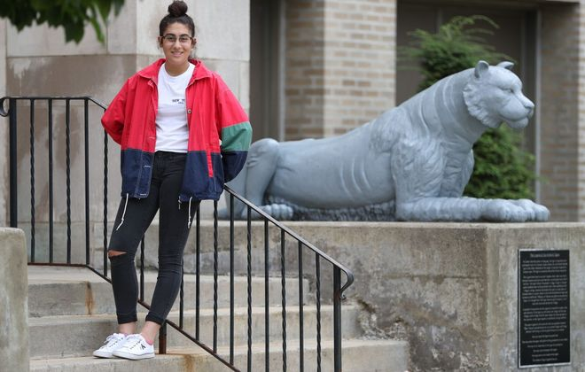 Olivia Cinquino, 17,  enjoys thrift shopping for items such as the jacket and jeans shown here. She was photographed outside Amherst Central High School, where she is a senior. (Sharon Cantillon/Buffalo News)