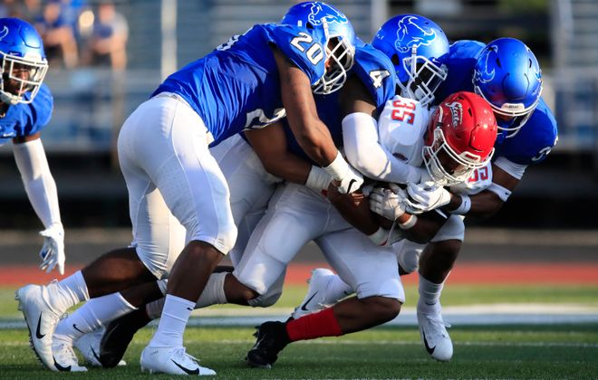 University at Buffalo defenders tackle Delaware State's Richard Harris. (Harry Scull Jr./Buffalo News)