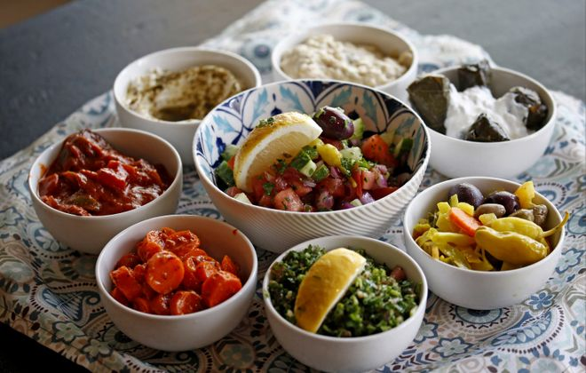 Traditional maza at Falafel Bar, from top: babaganoush, stuffed grape leaves, Yemeni pickle, tabouli, spicy Moroccan carrots, eggplant salad, hummus, with chopped Israeli salad in middle.   (Robert Kirkham/News file photo)