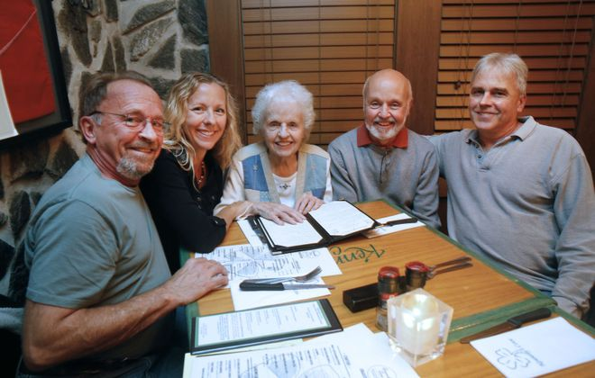 Jackie Steger, 90, center, surrounded by some of her children. From left, they are Brian, Trina Schiavitti, Craig and Bob. The family was at Kennedy's Cove on Main Street in Clarence marking Jackie Steger's 200th dinner with her son Craig. (Robert Kirkham/Buffalo News)