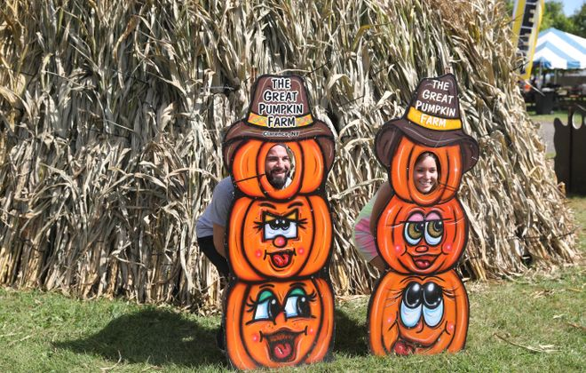 Tony Serra, left, and Shea Bacon of Guilford, Conn., pose in pumpkin cutouts  at the Great Pumpkin Farm in Clarence on Sunday, Sept. 16, 2018. (John Hickey/Buffalo News)