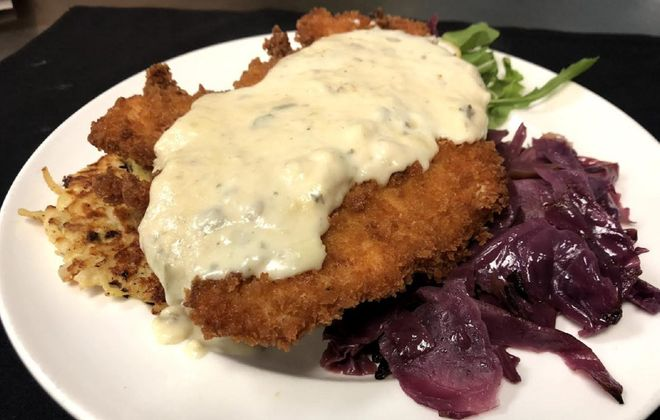 Chicken schnitzel topped with fontina cream sauce and served with potato pancakes and sweet and sour cabbage is popular at Schnitzel & Co. (Photo courtesy Schnitzel & Co.)