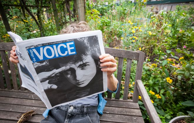 A reader views the last print issue of the Village Voice newspaper, featuring a Fred McDarrah photograph of Bob Dylan, in New York on Thursday, September 21, 2017. After 63 years the Village Voice will shut down, almost a year after it ceased its print publication. (Richard B. Levine/Sipa USA/TNS)