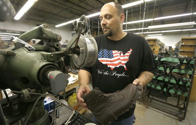 "Christopher Hall works on a shoe-making machine in the ""side lasting"" area of the plant at the  P.W. Minor shoe company in Batavia.  (Robert Kirkham/News file photo)"