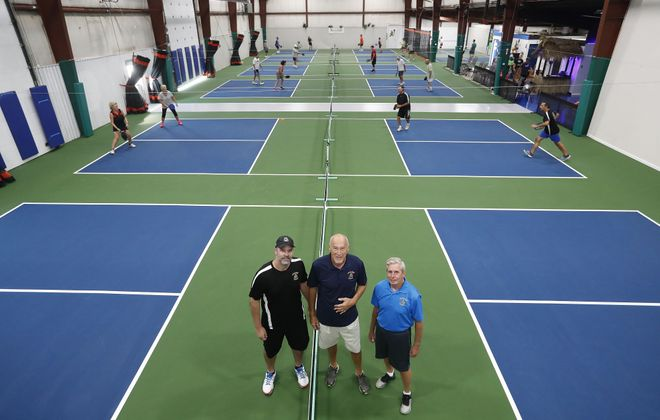 "Pickleball Island founder and ""mayor"" Ken Knight, center, enlisted the help of Jason Santerre, left, and David Miller, right, to help expand and run the pickleball center on Grand Island. Knight's brother, John, did much of the renovation work. (Mark Mulville/Buffalo News)"