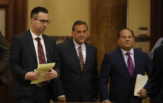 G. Steven Pigeon, center, leaves State Supreme Court with his lawyer, Paul J. Cambria Jr., after Pigeon entered a guilty plea to a charge of bribery. (Derek Gee/Buffalo News)