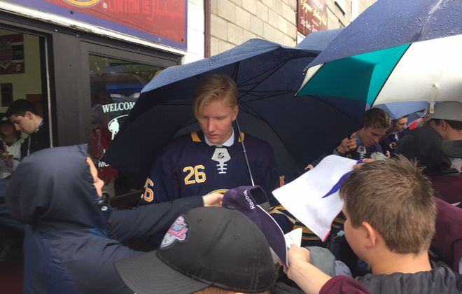 Rasmus Dahlin is mobbed by fans getting autographs as the Sabres walked a red carpet through the rain to enter Clinton Arena on Tuesday morning (Mike Harrington/Buffalo News).