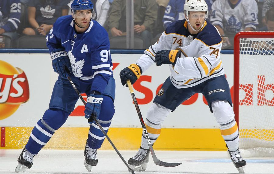 Rasmus Asplund of the Sabres (74) eyes the puck while keeping tabs on Maple Leafs center John Tavares (Getty Images).
