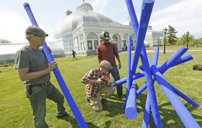 """Artist Shayne Dark, left, waits to place the next part of his piece, """"Tanglewood,"""" as assistants Colin Smith, drilling, and Eric Jones help with the installation at the Botanical Gardens in 2015. Dark's piece is coming to Amhert's Bassett Park next.  (Robert Kirkham/Buffalo News file photo)"""
