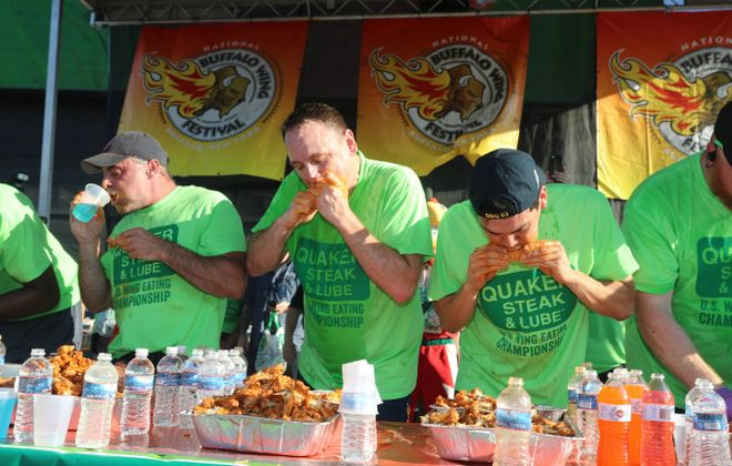 Joey Chestnut, center  a  professional wing eater, devours his way to first place. He ate 206 wings at the National Buffalo Wing Festival to earn his fifth straight title. (John Hickey/Buffalo News)