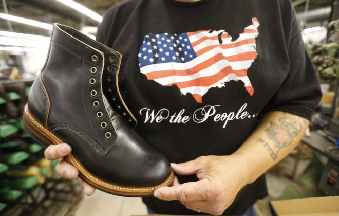 "An employee shows off the ""Black Hancock"" short boot at the  P.W. Minor  shoe company in Batavia.  (Robert Kirkham/News file photo)"