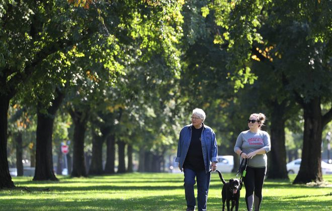 Beverly Schultz, left, her daughter Kelsey and her black lab/retriever Rhaegar walk along Chapin Parkway on a warm, sunny Monday. (Sharon Cantillon/Buffalo News)