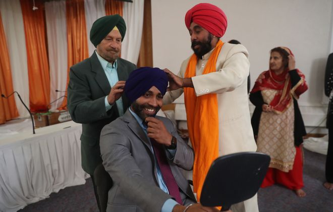 Yoga Singh, the priest at the Sikh Temple, right,  and Jagtar Singh Rajput, left, put finishing touches on a turban they just tied on Sibu Nair on Wednesday, Oct. 3, 2018.   (John Hickey/Buffalo News)
