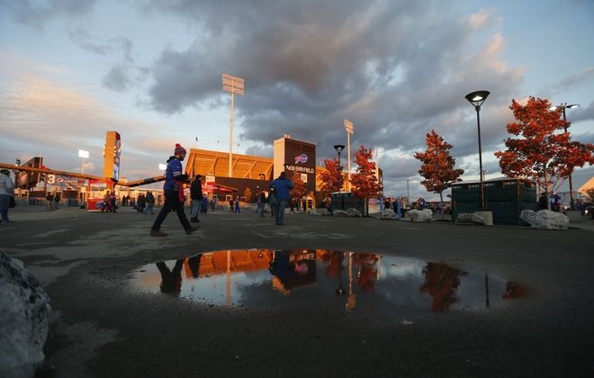 New Era field reflected in a puddle as skies clear for Bills fans tailgate in the parking lot before the game with the Patriots at New Era Field on Monday, Oct. 29, 2018.  (Mark Mulville/Buffalo News)