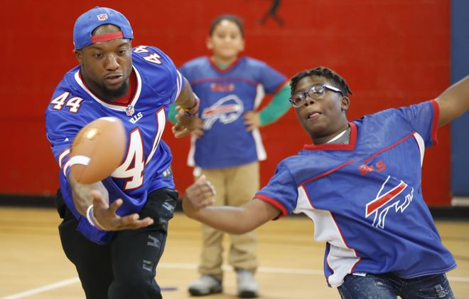 Bills linebacker Deon Lacey and 13-year-old Andre Mott try to make a catch during a game of flag football at the Boys and Girls Club Butler-Mitchell Clubhouse on Tuesday. (Derek Gee/Buffalo News)