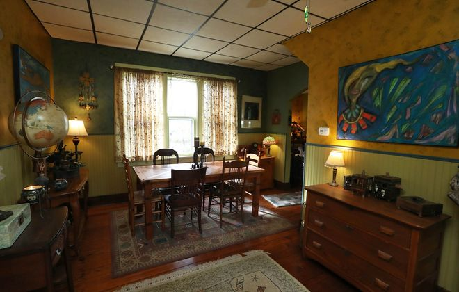 Barb and Charlie Mulloy live in a farmhouse in Clarence Hollow. This is the dining room; a painting by Barb Mulloy  can be seen on the right. (Sharon Cantillon/Buffalo News)
