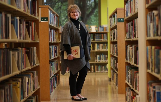 """Mary Jean Jakubowski is   director of the Buffalo & Erie County Public Library system. She was photographed this week at the Central Library  with her favorite book, """"What's Your Red Rubber   Ball?""""  by author/speaker Kevin Carroll. (Sharon Cantillon/Buffalo News)"""