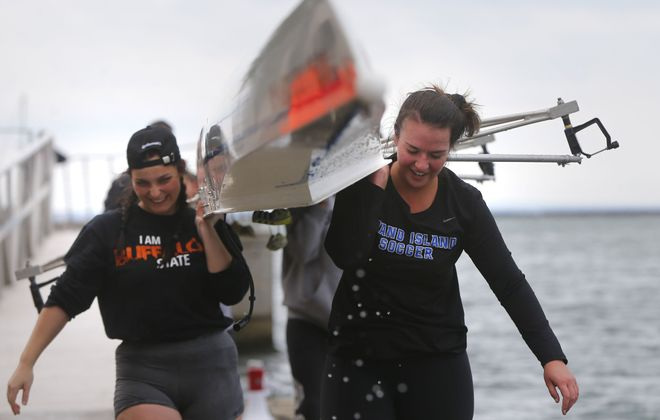 Gracie McNamara, right, Rachel Caiella, left and the rest of the SUNY Buffalo State women's collegiate novice team take their boat out of the water after racing in the Head of the Niagara & Wright Regatta at the West Side Rowing Club. (Mark Mulville/Buffalo News)