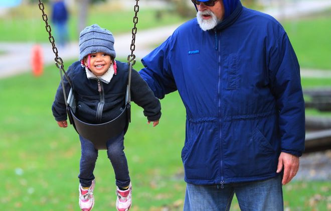 Pete Lang, of Buffalo, pushes his great niece Brook'Lyn Goldswieg, 3, on a swing at Shoshone Park in Buffalo on Saturday. Temperatures dipped late last week, and forecasts call for more bundling up this week. (Sharon Cantillon/Buffalo News)