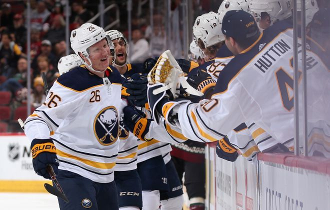 Rasmus Dahlin celebrates with teammates on the bench after scoring his first NHL goal Saturday in Arizona (Getty Images).