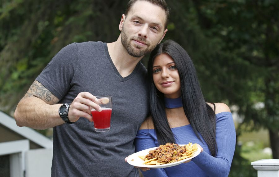 Brittany Kruse and Alex Miller, who have been dating for four years, started White Gloved Vegan last fall after the couple learned Miller, then 32, had a 99 percent blockage in a major artery. The health scare convinced them to change their eating habits. They're pictured holding Mexican quinoa chili, and  kombucha, both of which they made at home. (Robert Kirkham/Buffalo News)