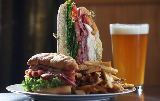 The legacy serves the Garlock's Deluxe Schiacciata, including sliced fresh mozzarella,  basil pesto mayonnaise, olive oil, lettuce, tomato, roasted red peppers, capicolla, mortadella and salami, on a toasted schiacciata roll. (Sharon Cantillon/Buffalo News)