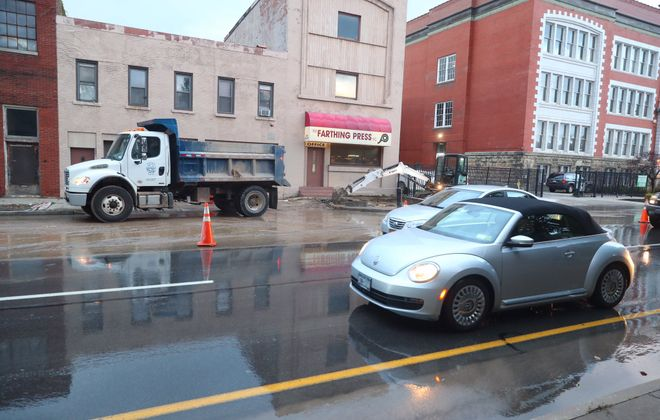 raffic goes over wet road as Buffalo water crews are on scene of a water main break on Oak Street near Genesee Street. (John Hickey/Buffalo News)