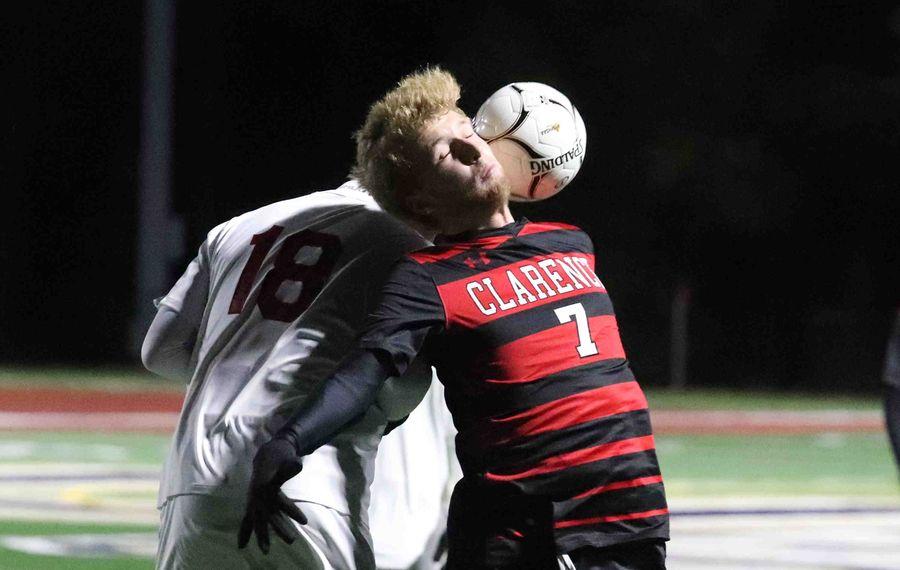 Clarence's Quinn Neelon heads the ball away from Hilton's Jack Gombatta. (James P. McCoy/Buffalo News)