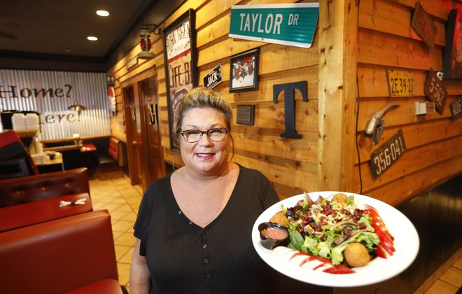 Anne Garner displays the cranberry goat cheese salad at Taylor's Tap & Grill on Niagara Falls Boulevard in Wheatfield. (Derek Gee/Buffalo News)