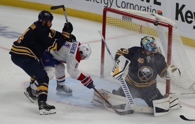 Buffalo Sabres goalie Carter Hutton watches as a shot goes off the crossbar as the Sabres' Zach Bogosian works on the Montreal Canadiens'  Brendan Gallagher, who ended up kicking the puck into the net, and getting goal called back. (John Hickey/Buffalo News)